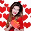 White caucasian woman with red lips giving a gift on heart shaped background.Valentines day — Stock Photo #63416537