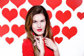 White caucasian woman with red lips holding a red lipstick on heart shaped background.Valentines day — Stock Photo