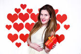 White caucasian woman with red lips holding a gift in one hand on heart shaped background.Valentines day concept — Stock Photo