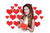 Bir hediye bir elinde tutan ve kalp gülümseyen kırmızı dudaklı beyaz beyaz kadın arka plan şeklinde. Sevgililer günü kavramı — Stok fotoğraf