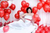 Young pregnant woman laying on a bed and holding a tummy red balloons around — Stock Photo