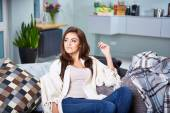 Young woman sitting on couch. — Stock Photo