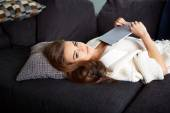 Cheerful woman lying on a cosy couch — Stock Photo