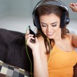 Cute smiling woman lying on couch while listening to music — Stock Photo #63587647