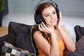 Linda mujer sonriente tumbado en el sofá mientras escucha música — Foto de Stock