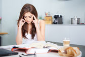 Young student woman with lots of books studying — Stockfoto