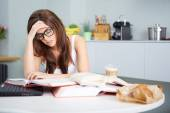 Happy young woman studying in kitchen — Stock Photo