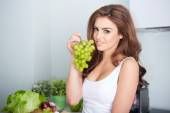 Happy young woman eating grape — Stock Photo