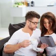 Woman with tablet and husband reading newspaper — Stock Photo #63985843