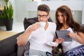 Woman with tablet and husband reading newspaper — Foto de Stock