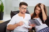Woman with tablet and husband reading newspaper — Stock Photo