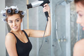 Young woman putting curlers in her hair, bathroom — Stockfoto