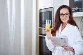 Woman reading the news while drinking orange juice — Stock Photo
