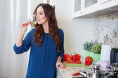 Cheerful young woman in apron on modern kitchen — Stock Photo