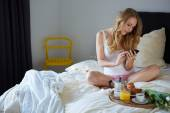 Young woman using cell phone in bed — Stock Photo