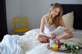 Happy smiling blond in white bed — Stock Photo
