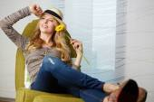 Young woman at home sitting on modern chair — Stock Photo
