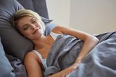 Woman resting in bed with hands beside her head — Stock Photo