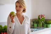 Happy young woman eating apples — Stock Photo