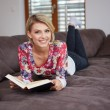 Woman enjoying reading a book at home lying on the sofa — Stock Photo #68883481