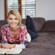 Woman enjoying reading a book at home lying on the sofa — Stock Photo #68883529