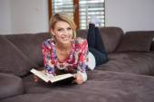 Woman enjoying reading a book at home lying on the sofa — Stock Photo
