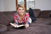 Woman enjoying reading a book at home lying on the sofa — Foto de Stock