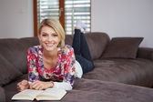 Woman enjoying reading a book at home lying on the sofa — ストック写真