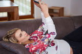 Attractive woman sitting on cosy couch in bright living room having a phone call — Fotografia Stock