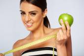 Beautiful young woman with green apple and measure tape — Stock Photo
