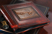 Leather photo album on expensive wooden with a reproduction of da Vinci on the table — Stock Photo