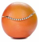 Elegant necklace with stones lying on grapefruit — Stock Photo