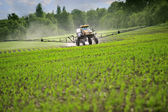 Tractor sprinkling young plants from pests at a farmer's field. — Stock Photo