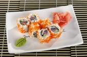 Sushi menu: a set of rolls with flying fish roe and avocado with wasabi and ginger on a plate — Stock Photo