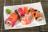Sushi menu: a set of rolls with assorted wasabi and ginger on a plate — Stockfoto