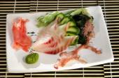 Sushi menu: sliced fish with slices of cucumber and seaweed on a plate — Stockfoto