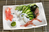 Sushi menu: shrimp with slices of cucumber and seaweed on a plate... — Stockfoto