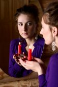 Woman with candle in front of a mirror. — Stockfoto