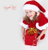 Cute little girl in a New Year's cap with a gift — Stock Photo