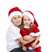 Cute girl and boy in Christmas hats with gifts — Stock Photo