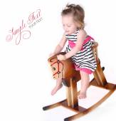 Pretty babe riding a horse toy — Stock Photo