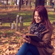 Redhead girl sitting on bench in park and reading book — Stock Photo #58774345