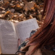 Redhead girl sitting on bench in park and reading book — Stock Photo #58775677