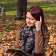 Redhead girl sitting on bench in park and reading book — Stock Photo #58776679