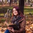 Redhead girl sitting on bench in park and reading book — Stock Photo #58776743