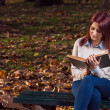 University girl sitting in park and reading a book — Stock Photo #58778039