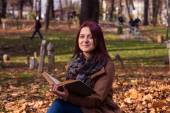 Redhead girl sitting on bench in park and reading book — Stockfoto