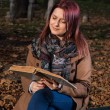 Redhead girl sitting on bench in park and reading book — Stock Photo #58788235