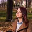 Redhead girl sitting on bench in park and reading book — Stock Photo #58788285