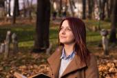 Redhead girl sitting on bench in park and reading book — Stock Photo